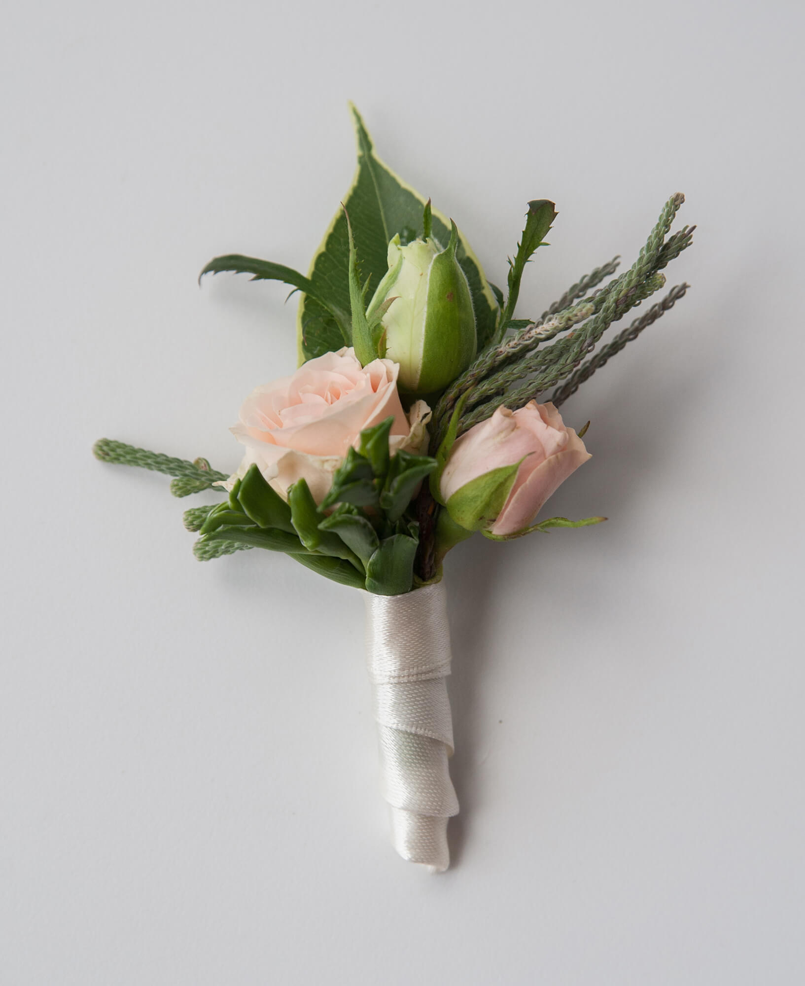 бутоньерка жениха из розовых и белых кустовых роз и брунии