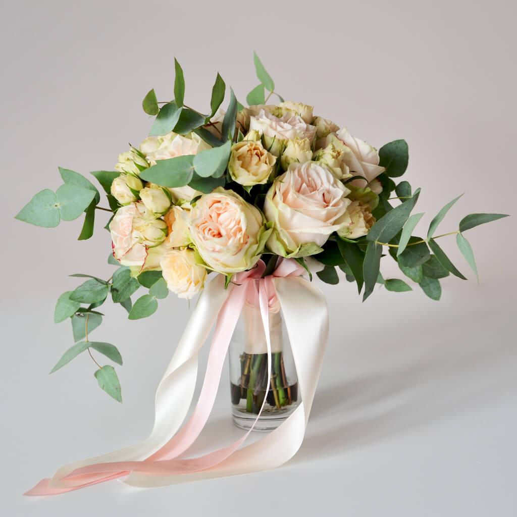Букет невесты из персиково-розовых пионовидных роз, персиковых кустовых роз и эвкалипта