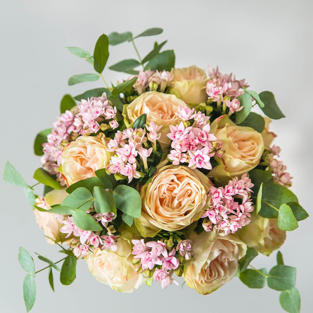 Букет невесты из персиковых пионовидных роз, бовардии и зелени (вид сверху)