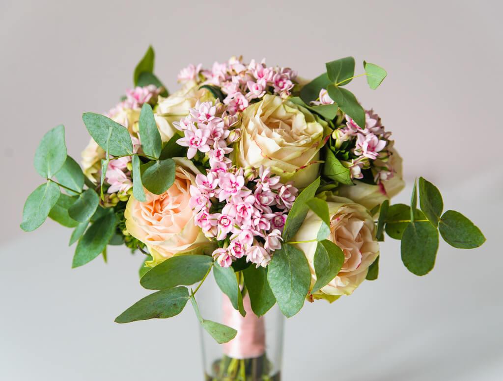 Букет невесты из персиковых пионовидных роз, бовардии и зелени