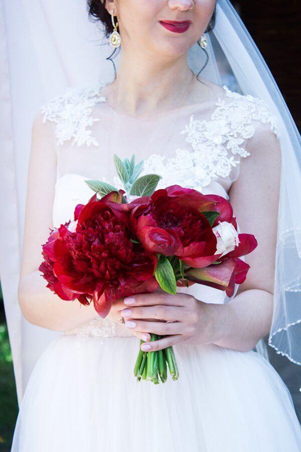 Свадебный букет из бордовых пионов, калл и розовых роз в руках невесты.