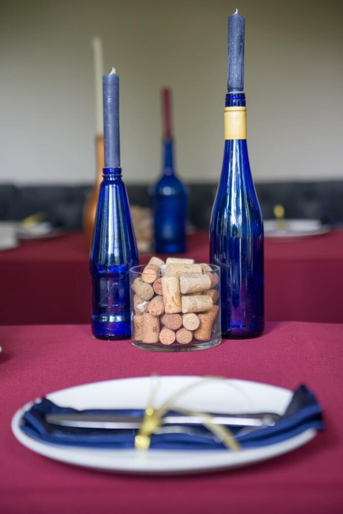 декор стола в винном стиле синими бутылками и салфетками