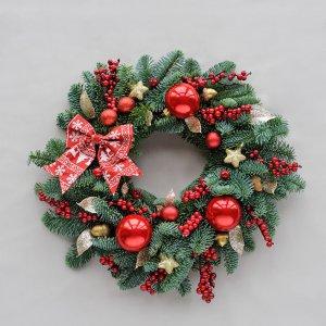 Рождественский венок из зеленых веток с красными шариками.