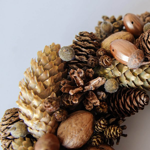 Рождественский венок из шишек, желудей и орехов крупным планом.