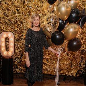 Девушка фотографируется с надувными шарами.