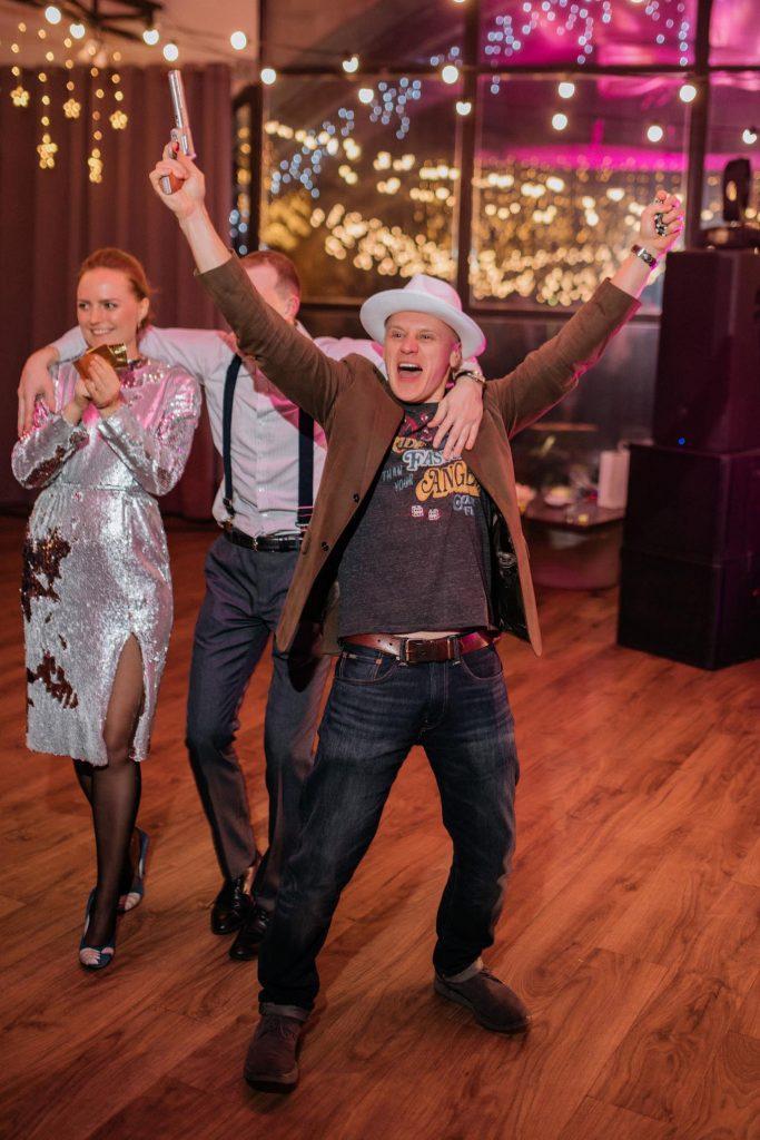 Мужчина в шляпе с пистолетом на гангстерской вечеринк