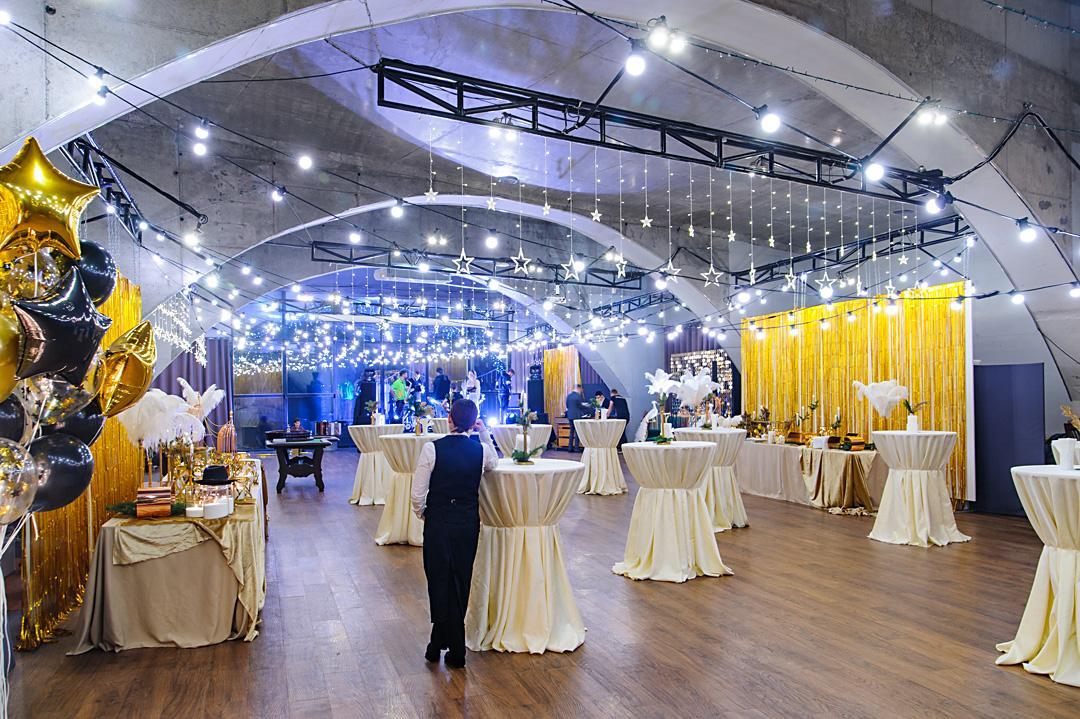 Зал АртПРИЧАЛа с столиками кейтеринга, потолок украшен гирляндами.