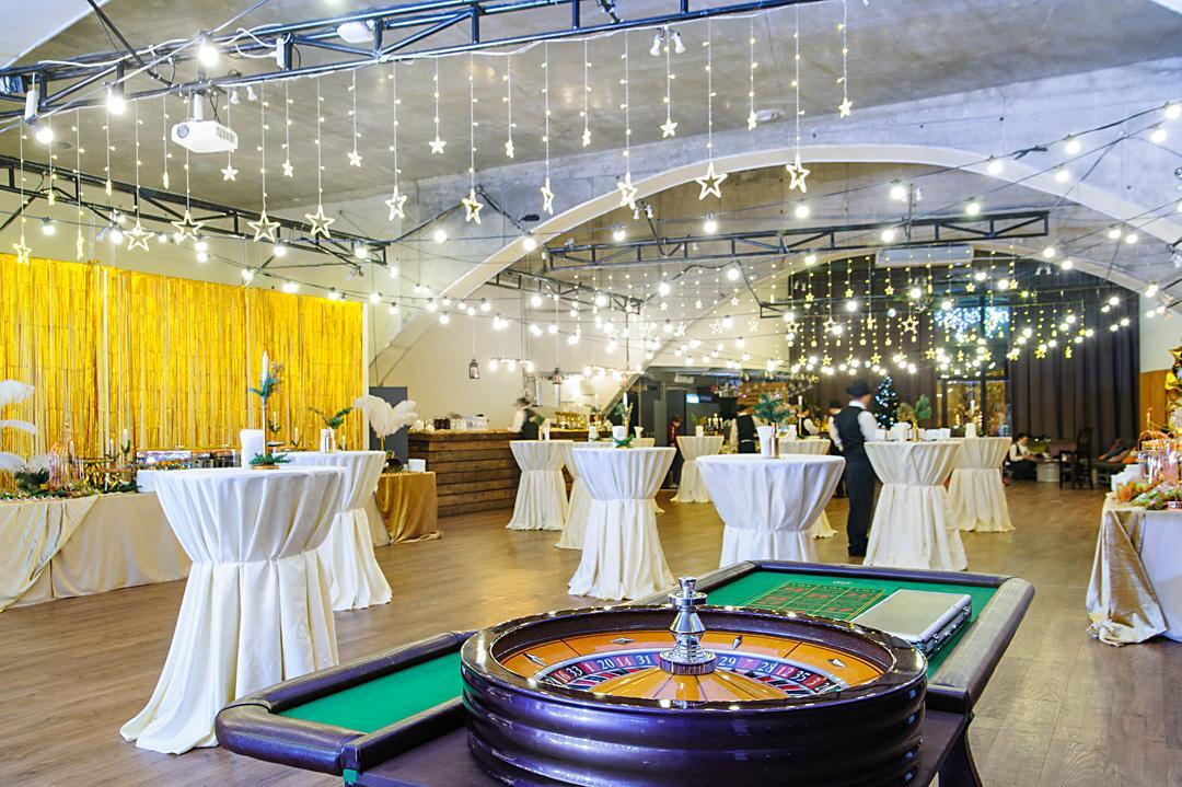 Зал АртПРИЧАЛа с рулеткой и столиками для еды.