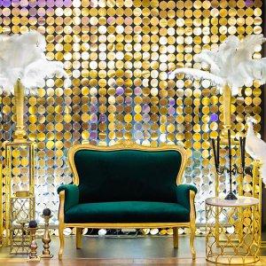 Фотозона с золотым фоном, изумрудным диваном, птицами и перьями в золотых вазах.
