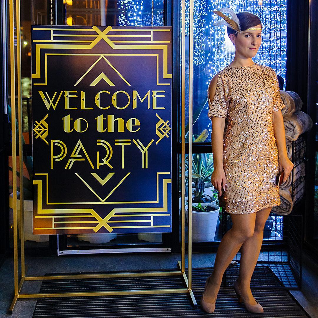 Банер в стиле «Великий Гэтсби» рядом с девушкой одетой в стиле 20-х.
