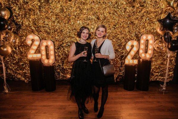 Две девушки позируют на фоне цифр 2020.