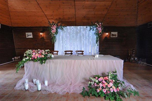 Президиум молодожен с двумя цветочными композициями на столе, композициями на заднике.