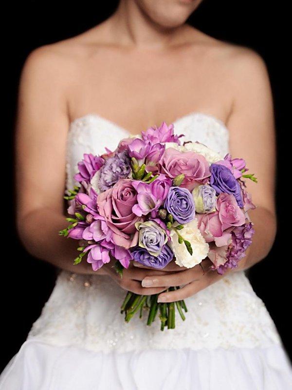 """Сиреневый свадебный букет невесты из роз """"Мемори Лейн"""" (""""Memory Lane""""), сиреневой и белой эустомы, сиреневой фрезии у невесты."""