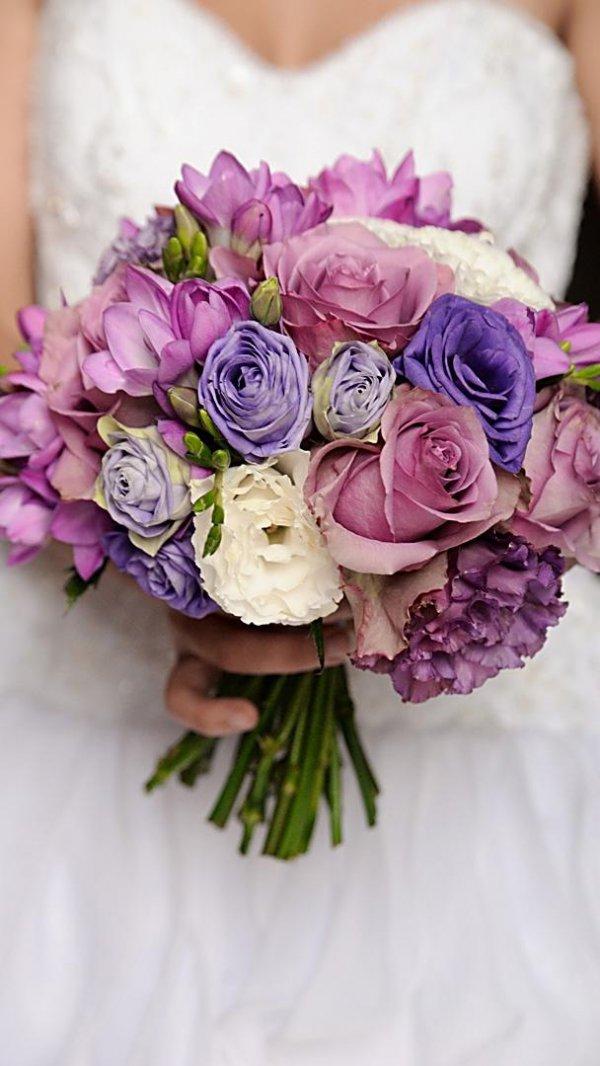 """Сиреневый свадебный букет невесты из роз """"Мемори Лейн"""" (""""Memory Lane""""), сиреневой и белой эустомы, сиреневой фрезии в руках"""