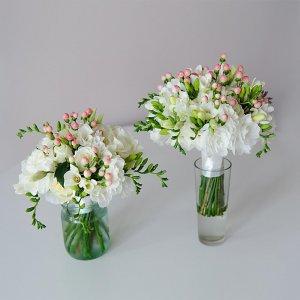 Белый букет невесты из эустомы, фрезии, розы и гиперикума (справа) и букет дублер (слева)