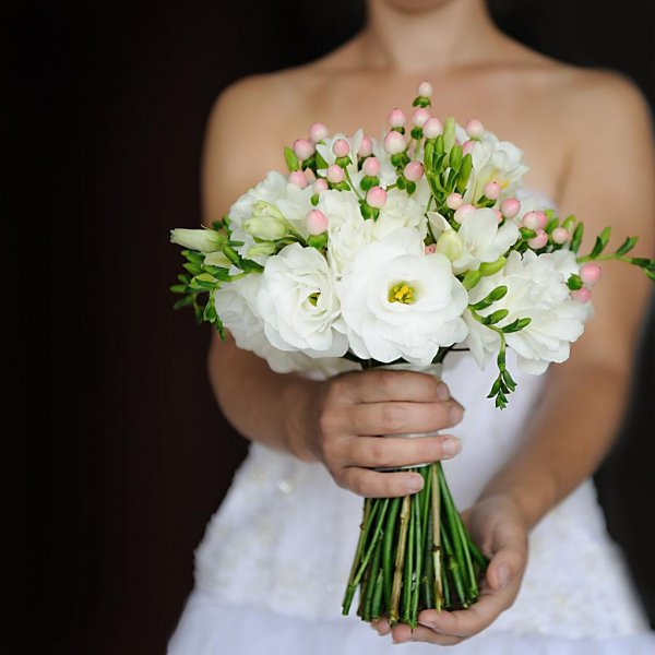 Белый букет из эустомы, фрезии, розы и розового гиперикума в руках у невесты