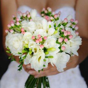 Белый свадебный букет из роз и эустомы в руках у невесты