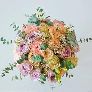 Букет невесты в нежно-розовых пудровых тонах из роз, эустомы, хамелациума, эвкалипта вид сверху.