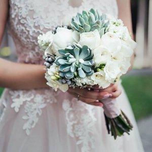 Свадебный букет из белых пионовидных роз, фрезии, брунии, маттиолы, эхеверии и фрезии в руках невесты