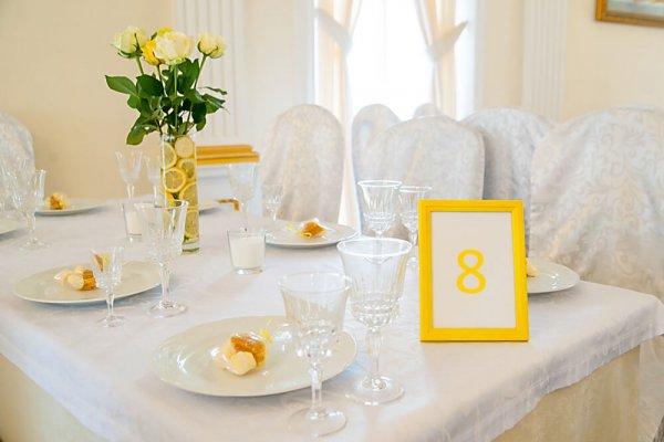 Стол гостей на свадьбе в лимонном стиле цветочной композицией и номером.