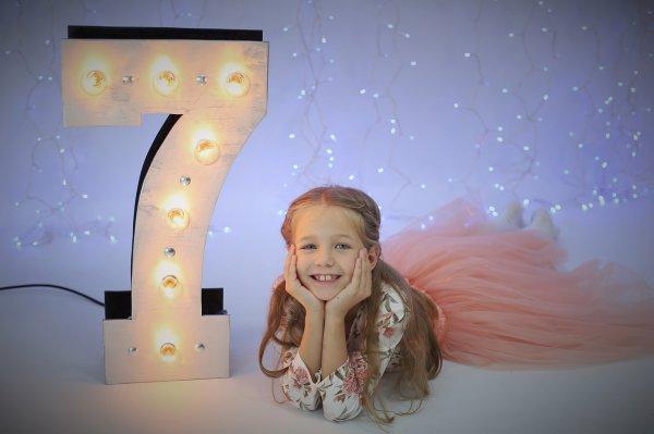 """Объемная цифра """"7"""" с светящимися лампочками и девочка на фотозоне"""