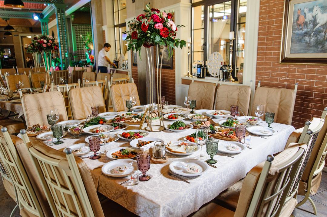 Квадратный стол ресторана накрыт для гостей. Сервировка стола с цветочной композицией на высокой подставке посередине.