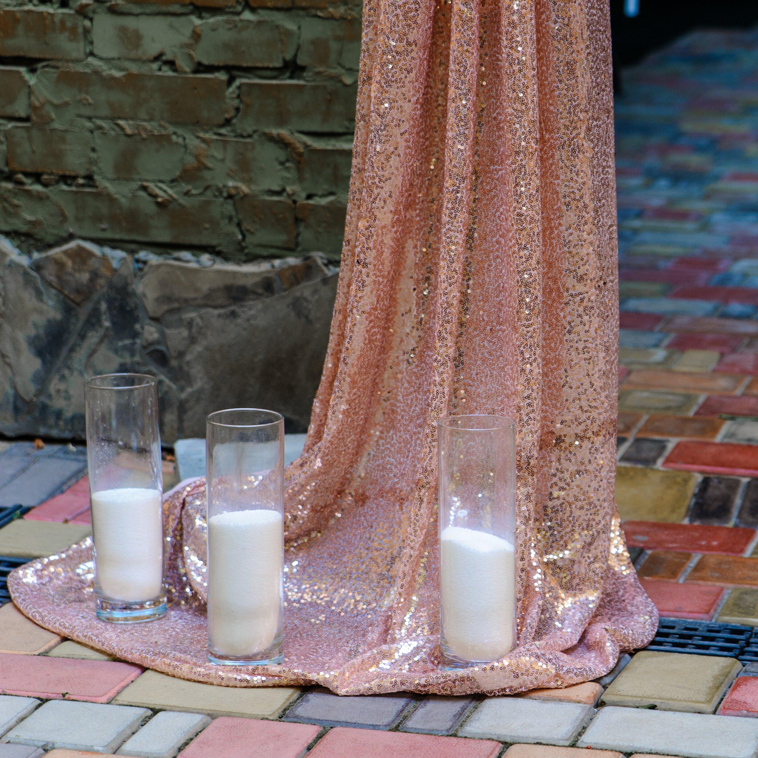 Колбы с насыпными свечами и пайеточная ткань украсили арку.