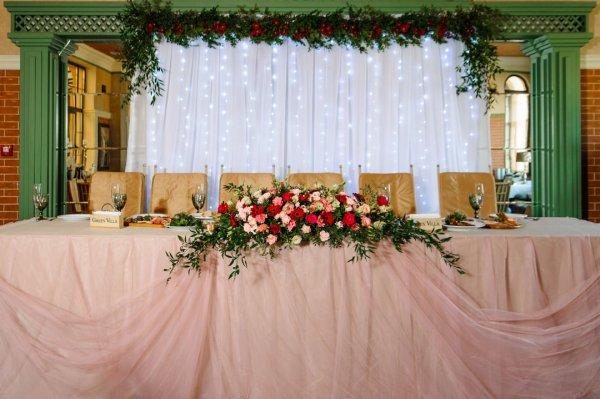Президиум молодоженов, цветы на столе молодоженов и ширма из белой ткани