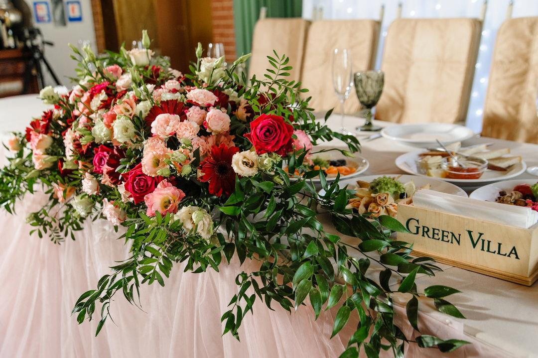 Цветочная композиция из живых цветов на столе молодоженов