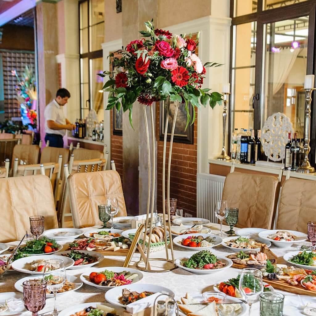 Стол гостей с цветочной композицией из живых цветов и зелени на высокой подставке.
