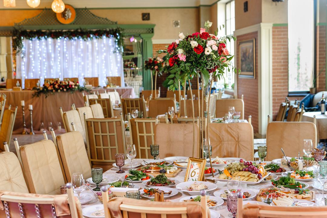 Банкетный зал GreenVilla c свадебным столом и цветочной композиций на подставке на нем