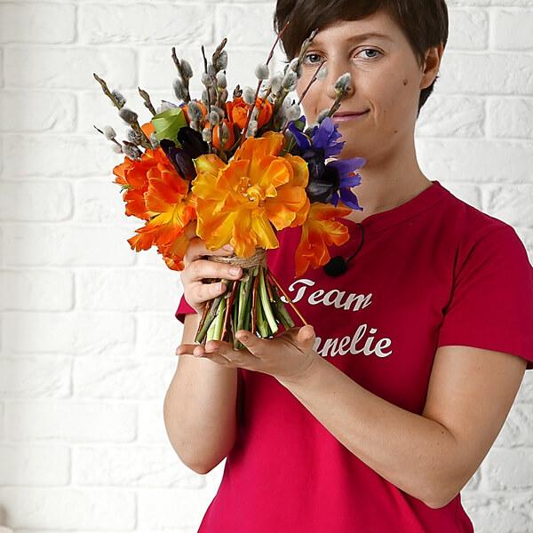 Весенний букет с оранжевыми тюльпанами держит в руках флорист.