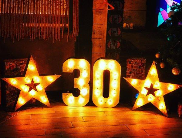 """Фотозона из двух звезд с лампочками и цифры """"30"""" по середине"""