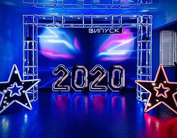 Неоновая RGB фотозона с цифрами 2020 по середине и неоновыми звездами по бокам.