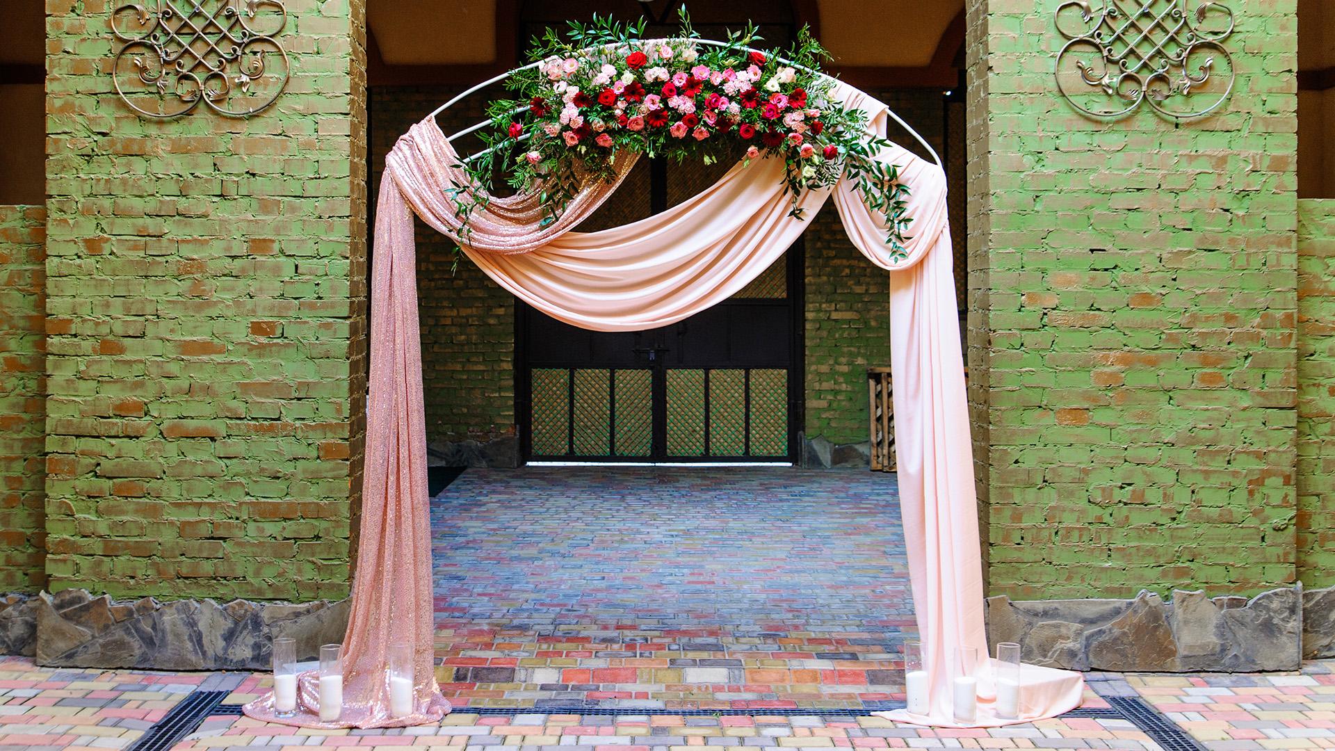Свадебная арка украшена живыми цветами.