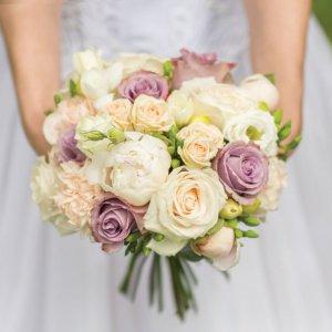 Букет невесты с пионами, розами, гвоздиками и фрезией в руках невесты