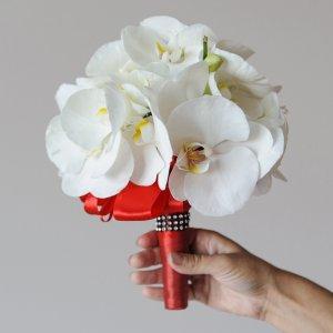 Свадебный букет из белой орхидеи с красной ручкой в руке