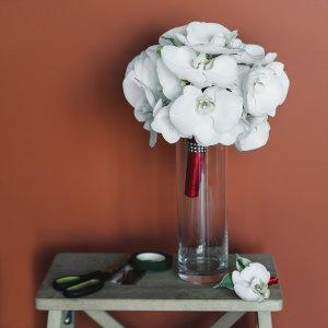 Свадебный букет из белой орхидеи с бутоньеркой на столике