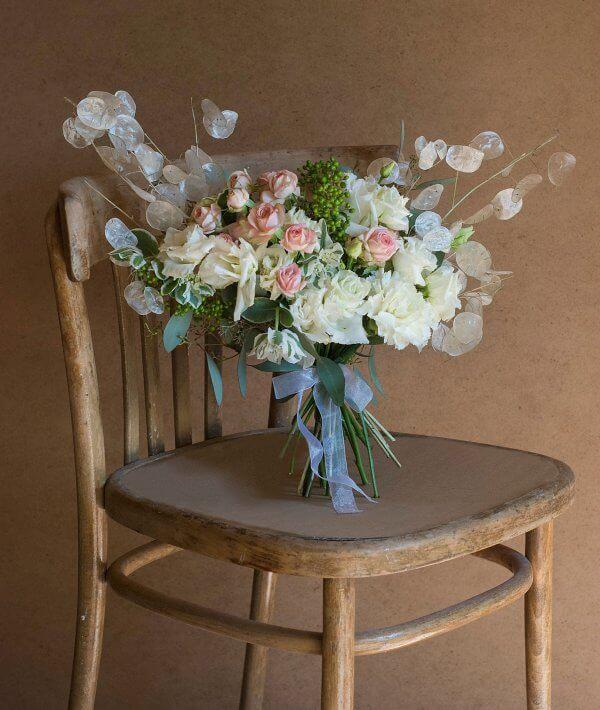 Букет невесты с сухоцветами розой, эустомой, гвоздикой, лунарией лежит на стуле