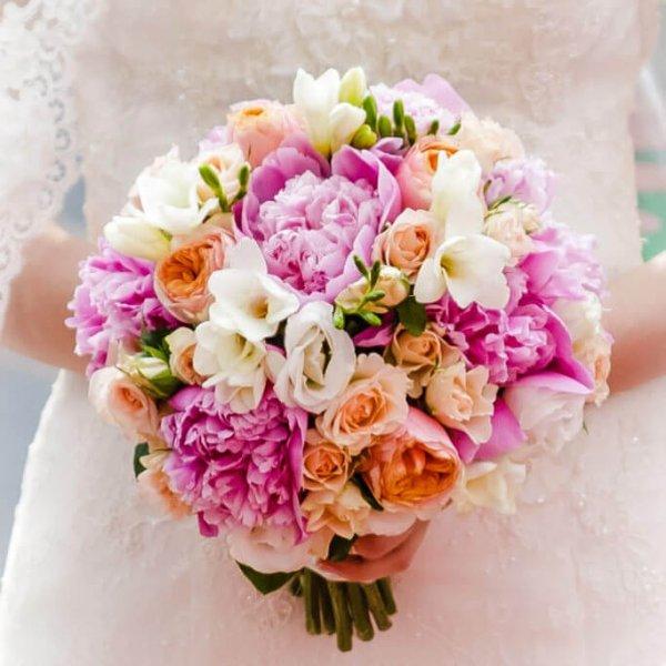 Букет в руках невесты в малиново-персиковой цветовой гамме