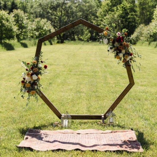 Деревянная арка-многоугольник с декором из цветочной композиции в теплых тонах