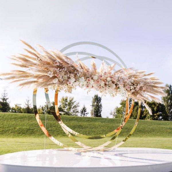 Конструкция в виде золотых колец, с декором из живых цветов
