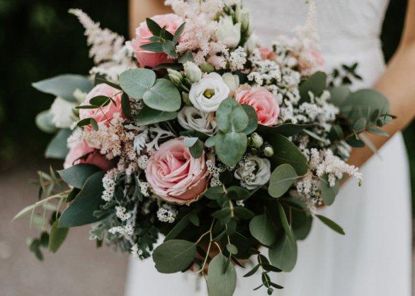 Бело-розовый букет невесты из роз, эвкалипта, эустомы держит в руках невеста