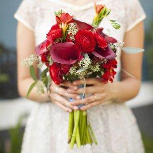 Свадебный букет из калл, фрезии, ранункулюсов, эвкалипта в руках невесты