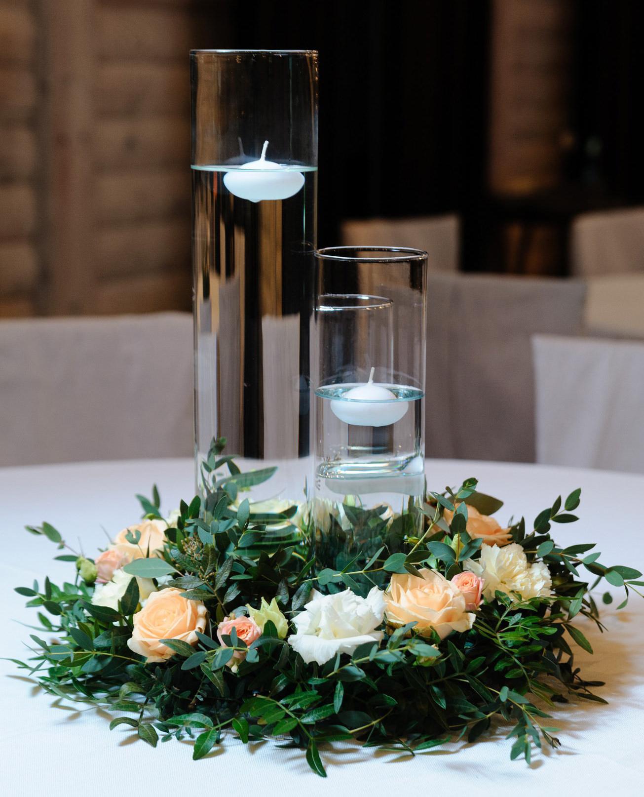Венок из зелени и живых цветов на столы гостей с высокими колбами для плавающих свечей