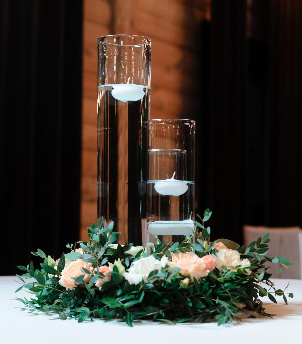 Венок из зелени и живых цветов на столы гостей с высокими колбами посередине