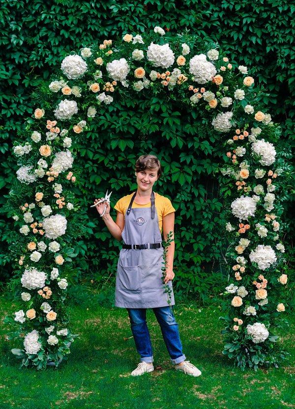 Девушка флорист Pion Bouton под свадебной аркой