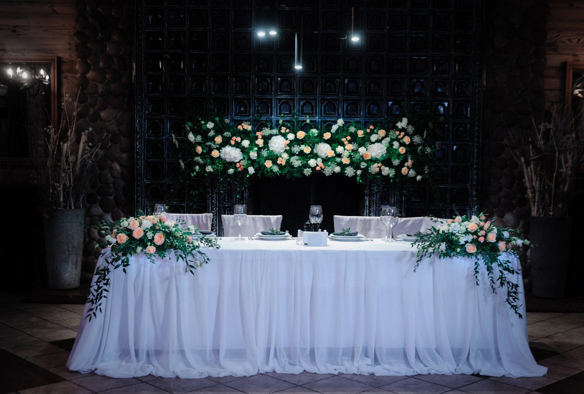 Президиум молодожен украшенный живыми цветами на столе и цветочным карнизом позади