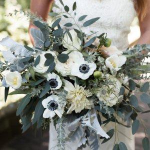 Свадебный букет растрепыш с георгинами, розами, анемонами в руках невесты