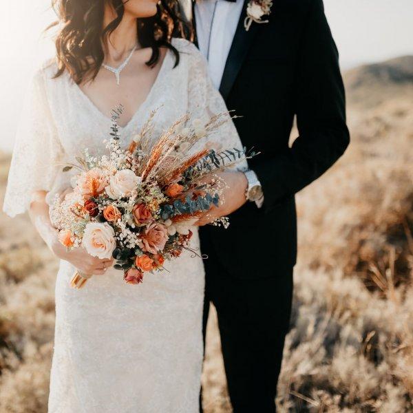 Рустикальный осенний свадебный букет из роз и сухоцветов и пара новобрачных в поле